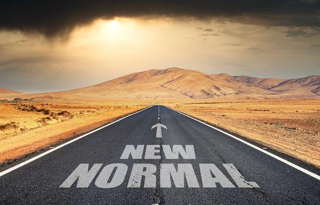 Litery na dnie pustynnej drogi o zachodzie słońca, wskazujące drogę do nowej normalności po pandemii.