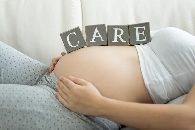 """Litery na drewnianych klockach tworzące słowo """"troska"""" na brzuchu kobiety w ciąży"""