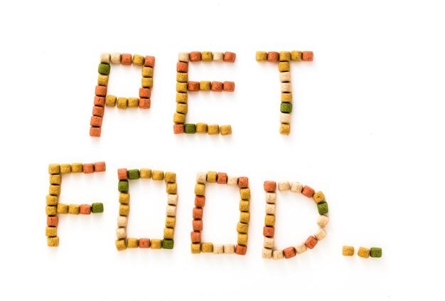 Litery z suchej karmy dla zwierząt domowych na białym tle