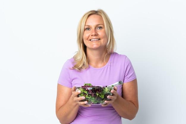 Litewska kobieta w średnim wieku na białej ścianie trzyma miskę sałatki z happy wypowiedzi