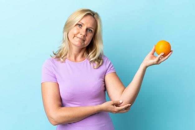 Litewska kobieta w średnim wieku na niebieskim ścianie trzyma pomarańczowy