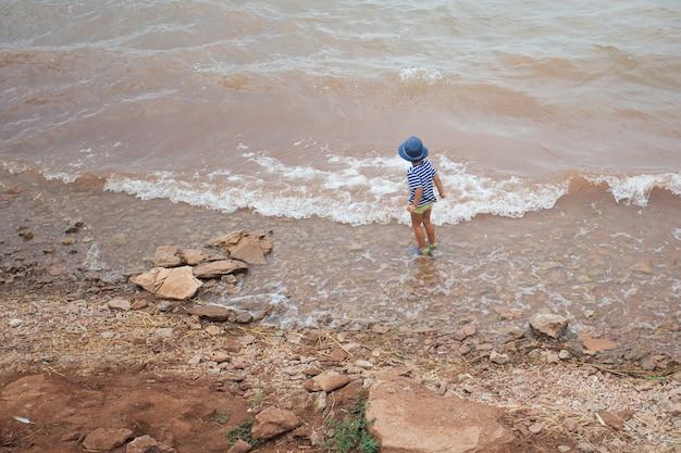 Litlle chłopiec w niebieskim kapeluszu stojący na morzu