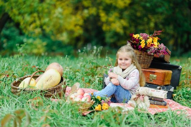 Litlle dziewczyny obsiadanie na koc na trawie