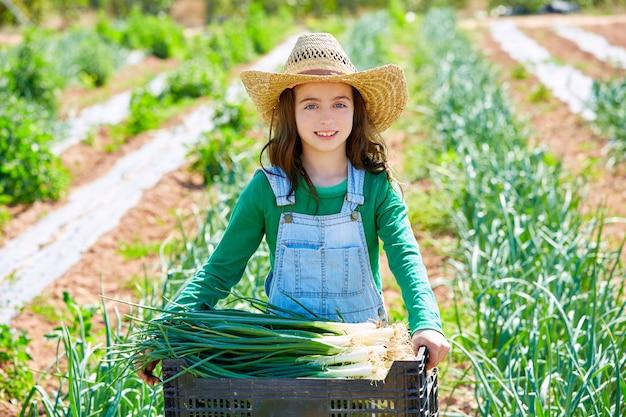 Litte kid rolnik dziewczyna w sadzie zbiorów cebuli
