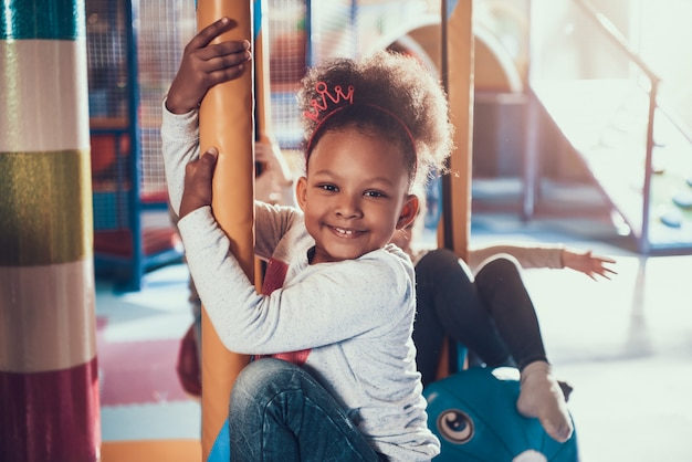Little african american girl riding carousel