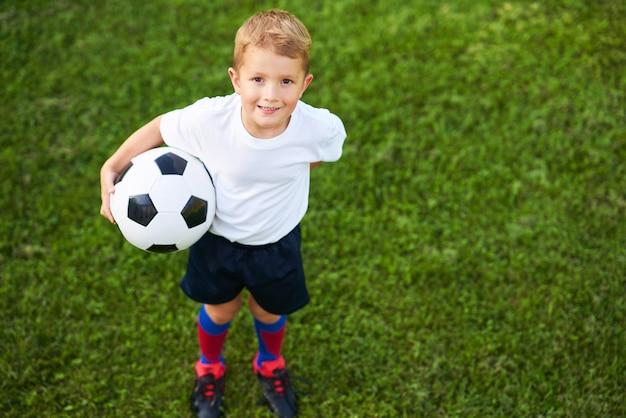 Little boy ćwiczy piłkę nożną na świeżym powietrzu