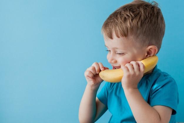 Little boy próbuje rozmawiać przez banana zamiast przez telefon.