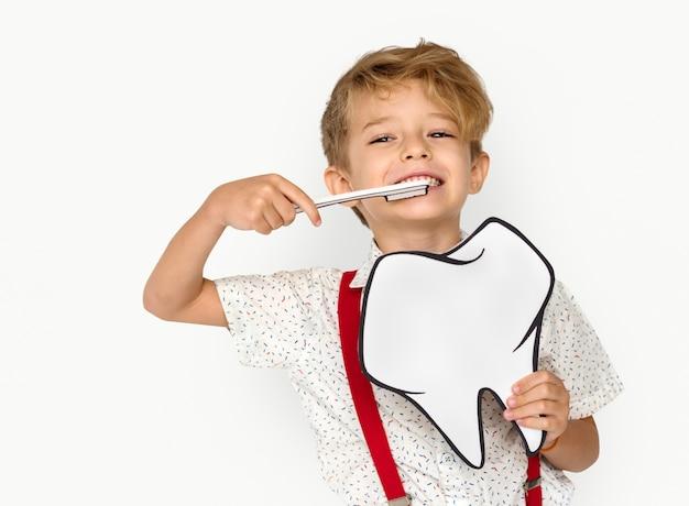 Little boy szczotkowanie zęby trzyma papercraft ząb