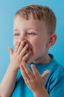 Little boy trzyma banana i je na błękitnym tle, jedzeniu, diecie i zdrowym łasowania pojęciu ,.