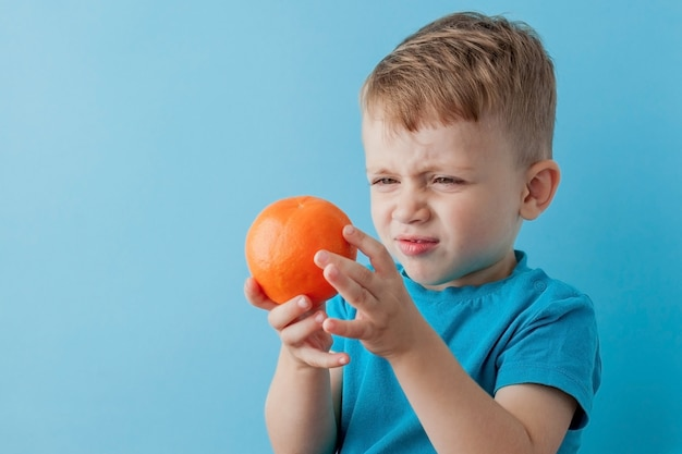 Little boy trzyma pomarańcze w jego rękach na błękit ścianie, diecie i ćwiczeniu na dobre zdrowie pojęcie