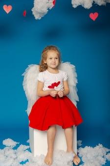 Little cute girl aniołów na niebieskim tle na walentynki