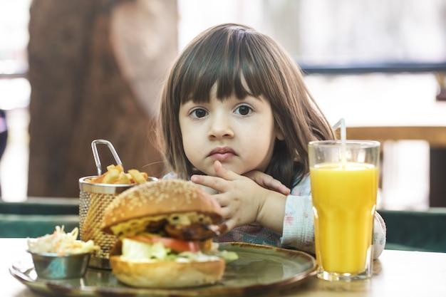 Little cute girl jedzenie kanapki fast food z frytkami i sokiem pomarańczowym w kawiarni. koncepcja fast food.