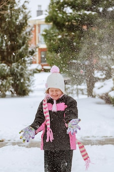 Little girl gry ze ?niegiem happy laughing dziewczynka ubrana w fioletow? kurtk? puchow?