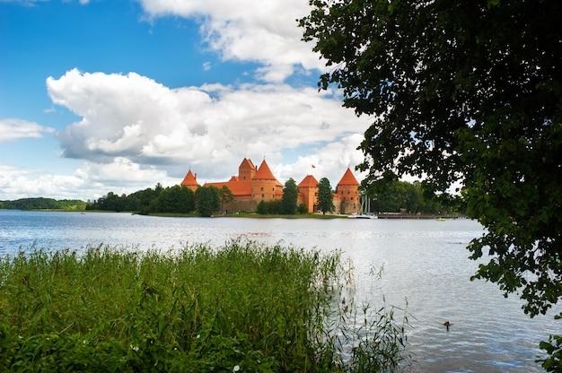 Litwa. widok na zamek w trokach po drugiej stronie jeziora i biały jacht pod żaglami