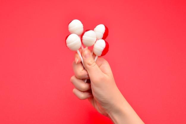 Lizak w kobiecej dłoni na czerwono