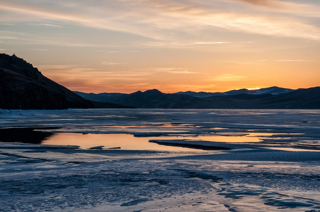 Lód i woda w pobliżu góry na zamarzniętym jeziorze bajkał przed wschodem słońca
