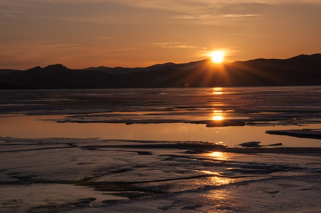 Lód i woda w pobliżu góry na zamarzniętym jeziorze bajkał. zachód słońca