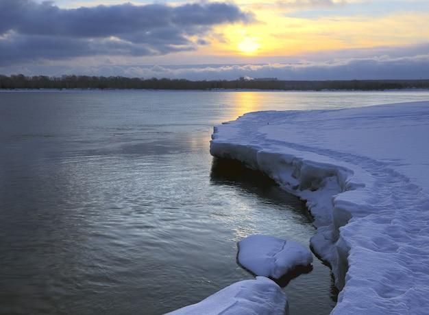 Lód na brzegu obu o wschodzie słońca niebieski śnieg i oderwany lód łuk linii brzegowej rzeki