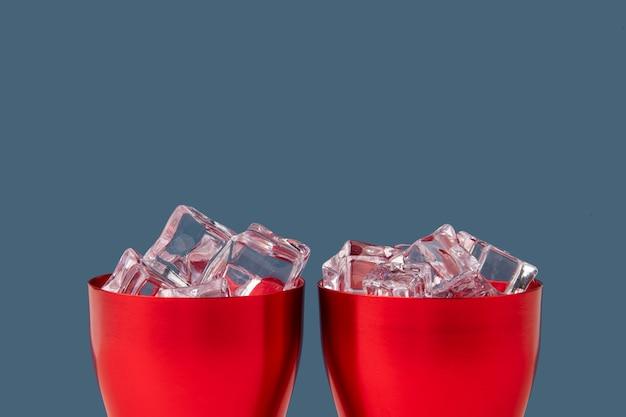Lód na czerwonym kubku z niebieskim tłem