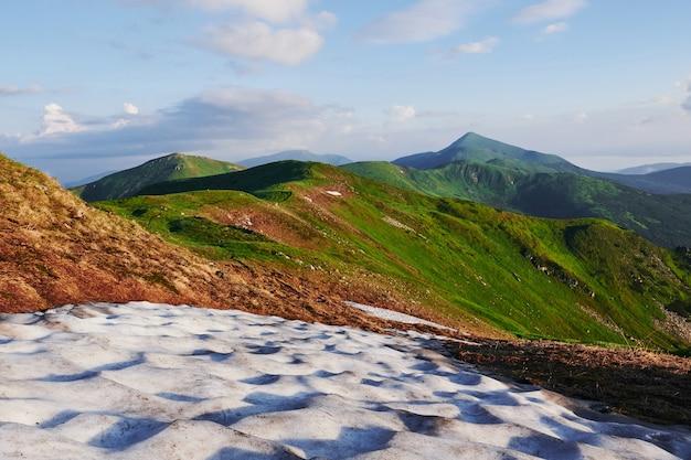 Lód na trawie. majestatyczne karpaty. piękny krajobraz. widok zapierający dech w piersiach.