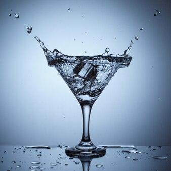 Lód w szkle z pluskiem wody na niebieskiej powierzchni na stole z odbiciem