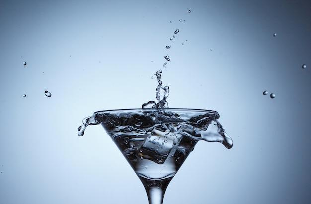 Lód w szkle z pluskiem wody na niebieskiej powierzchni