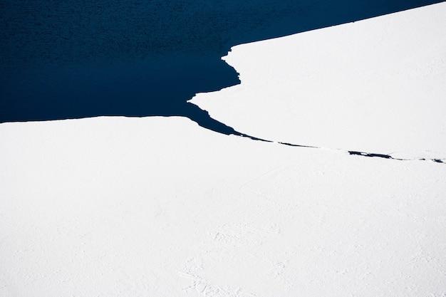 Lód z białym śniegiem i błękitną wodą jeziora. widok z lotu ptaka drona. streszczenie tle przyrody. jezioro bajkał, syberia, rosja.