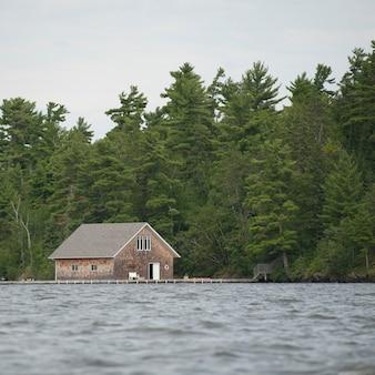 Łódkowaty dom przy linią brzegową przy jeziorem drewna, ontario