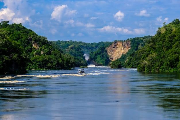 Łódkowaty żeglowanie na wodzie po środku falez z drzewami i roślinami z niebieskim niebem
