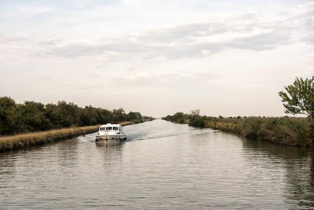 Łódkowaty żeglowanie w kanale w chmurnym dniu