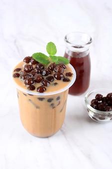 Lodowa czekolada mleczna lub kawa z perłami boba tapioki na wierzchu z liściem mięty jako dekoracją