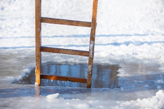 Lodowa dziura w zimowym jeziorze z drewnianą drabiną. święto chrztu jezusa.
