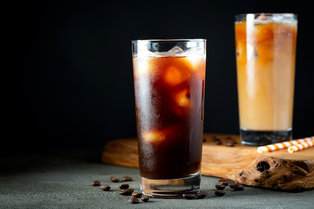 Lodowa kawa w wysokiej szklance z kremem polanym.
