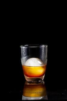 Lodowa kula w szklance whisky na odblaskowym czarnym stole.