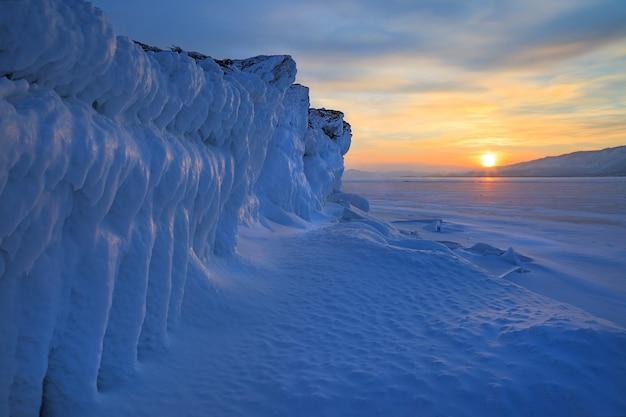 Lodowa ściana zamarzniętych skał na zachód słońca, piękny zimowy krajobraz