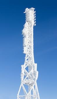 Lodowata antena stacji bazowej pokryta śniegiem. wieża witryny komórkowej na wzgórzu moutain.