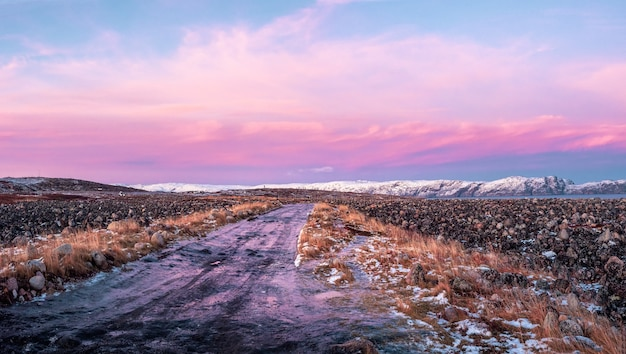 Lodowata zimowa droga przez tundrę w teriberce. niesamowity kolorowy krajobraz arktyki.