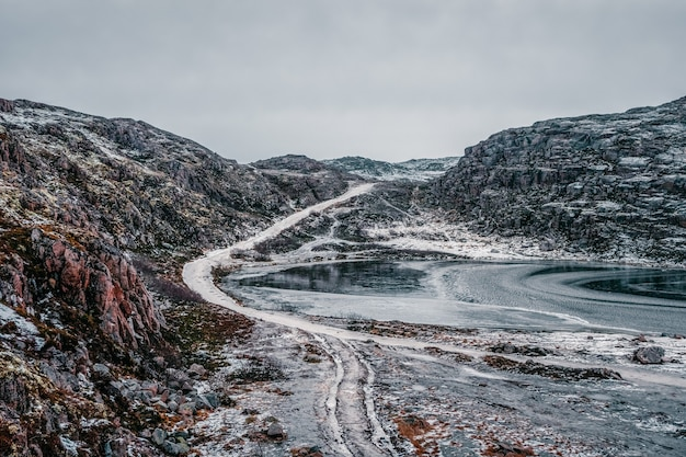 Lodowata zimowa droga przez tundrowe wzgórza w teriberce. niesamowity kolorowy krajobraz arktyki.