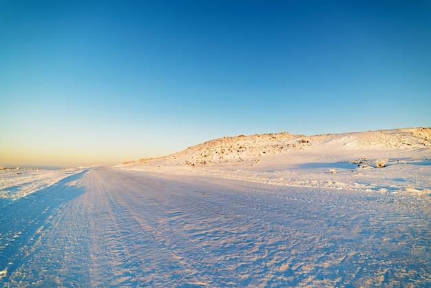 Lodowata zimowa droga wśród ośnieżonych gór