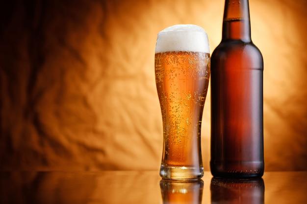 Lodowaty kufel piwa w nieoznakowanej butelce i szklance ze spienioną głową i musującym tłem na rustykalnym tle tekstury