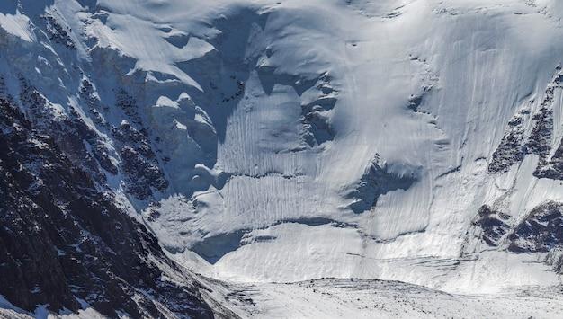 Lodowce i śnieg na stromym zboczu, podróżowanie po górach, wspinaczka