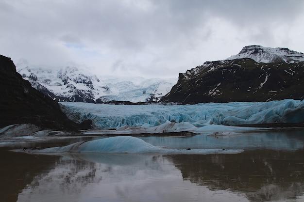Lodowiec otoczony wzgórzami pokrytymi śniegiem i odbijający się w wodzie na islandii