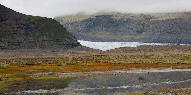 Lodowiec w mglistej chropowatej dolinie górskiej, z ciałem wodnym odzwierciedlającym niebo