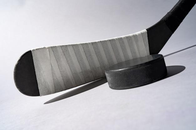 Lodowy hokejowy krążek hokojowy i hokejowy kij na odosobnionym białym tle