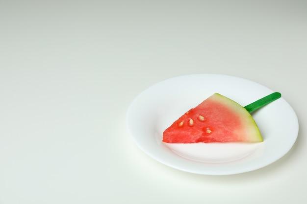 Lodowy kij z plasterkiem arbuza na talerzu na białym tle