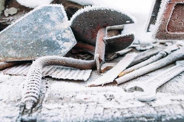 Lodowy kot na zewnątrz z szronem na śniegu. pozostawione na zewnątrz narzędzia zimą. zimno, wczesne przymrozki, koncepcja szronu