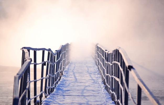 Lodowy most z poranną mgłą zimą