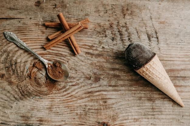 Lody czekoladowe w rożku na drewnianym tle. słodki deser na stole. kompozycja z lodami słodka przekąska. lody z cynamonem i czekoladą. laski cynamonu