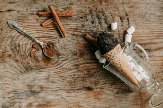 Lody czekoladowe w rożku na drewnianym tle. słodki deser na stole. kompozycja z lodami. słodka przekąska. lody z cynamonem i czekoladą