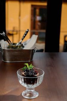 Lody czekoladowe z dżemem na stole. lody czekoladowe z konfiturą jagodową w szklanej filiżance